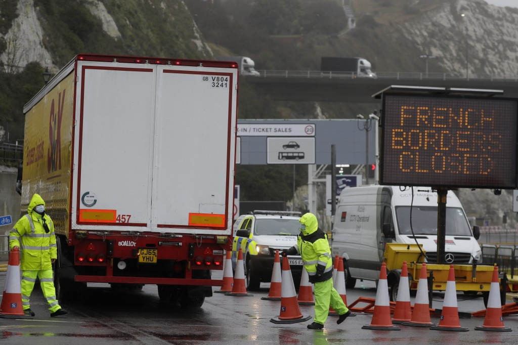 Security guard the entrance to the ferry terminal in Dover, England, Monday, Dec. 21, 2020, after the Port of Dover was closed and access to the Eurot...