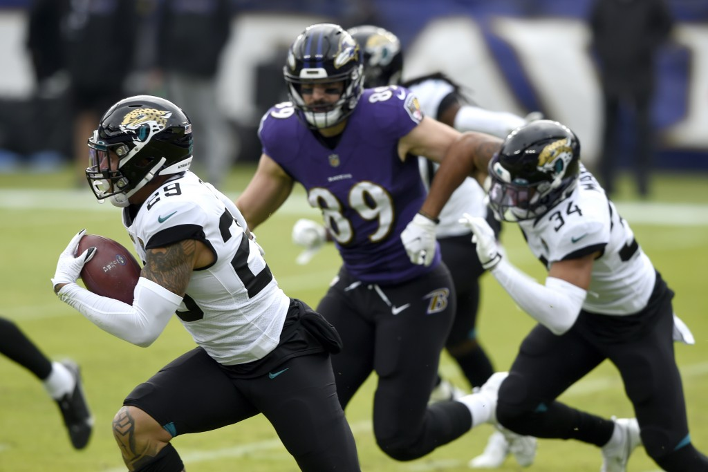 Jacksonville Jaguars safety Josh Jones, left, runs with the ball after intercepting a pass from Baltimore Ravens quarterback Lamar Jackson, not visibl...