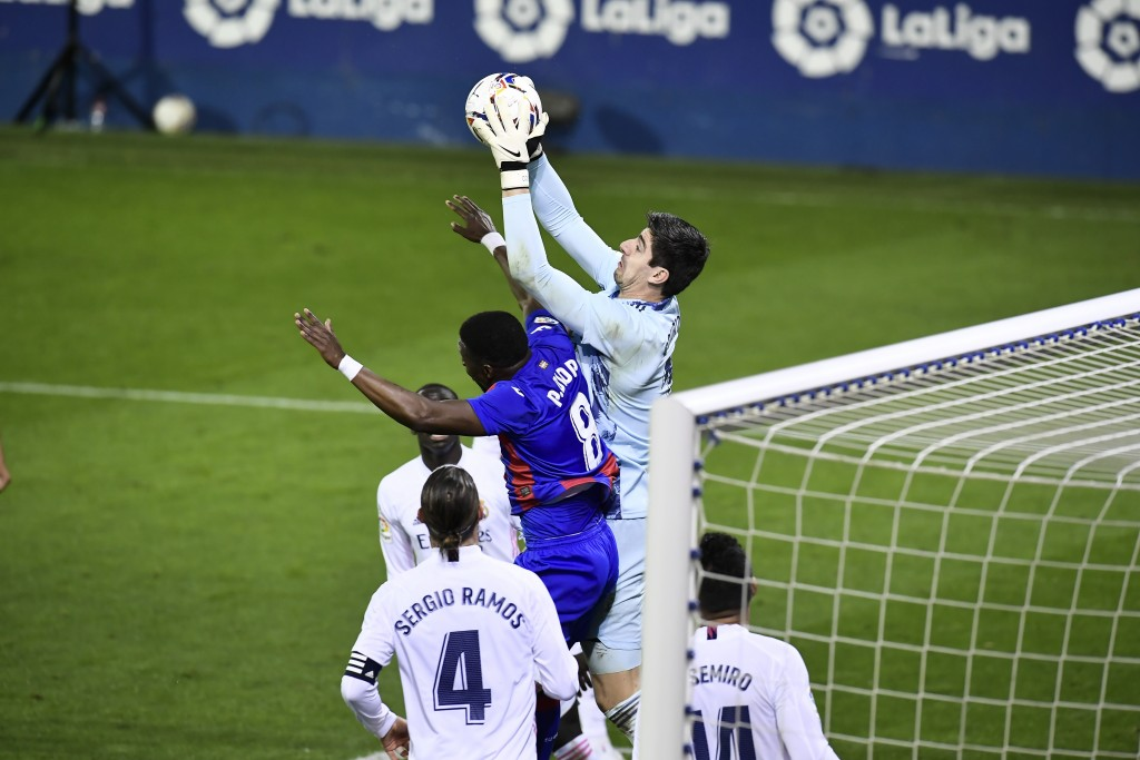 Real Madrid's goalkeeper Thibaut Courtois, controls the ball in front Eibar's Pape Diop during the Spanish La Liga soccer match between Eibar and Real...