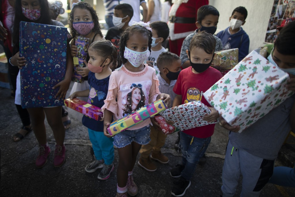 "Children hold Christmas gifts donated by the volunteer group Un Juguete, Una Buena Noticia,"" or One Toy, One Good News, in Caracas, Venezuela, Friday,..."