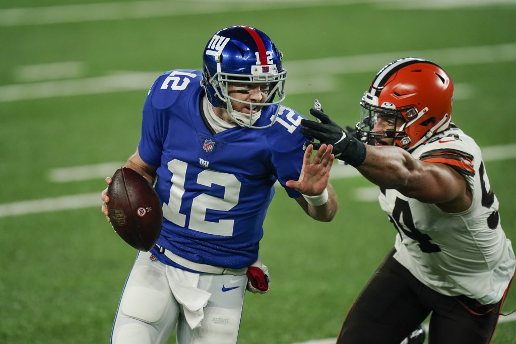 New York Giants quarterback Colt McCoy (12) evades Cleveland Browns' Olivier Vernon (54) during the first half of an NFL football game, Sunday, Dec. 2...