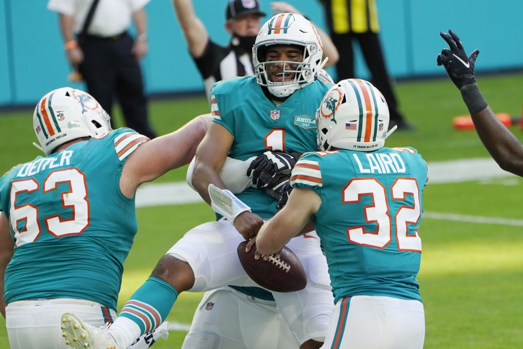 Miami Dolphins offensive guard Michael Deiter (63) and running back Patrick Laird (32) celebrate a touchdown by quarterback Tua Tagovailoa (1), center...