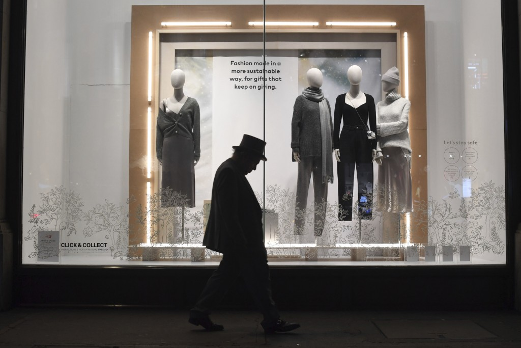 A man walks past a closed shop on Regent Street in central in London, Sunday, Dec. 20, 2020.  Millions of people in England have learned they must can...