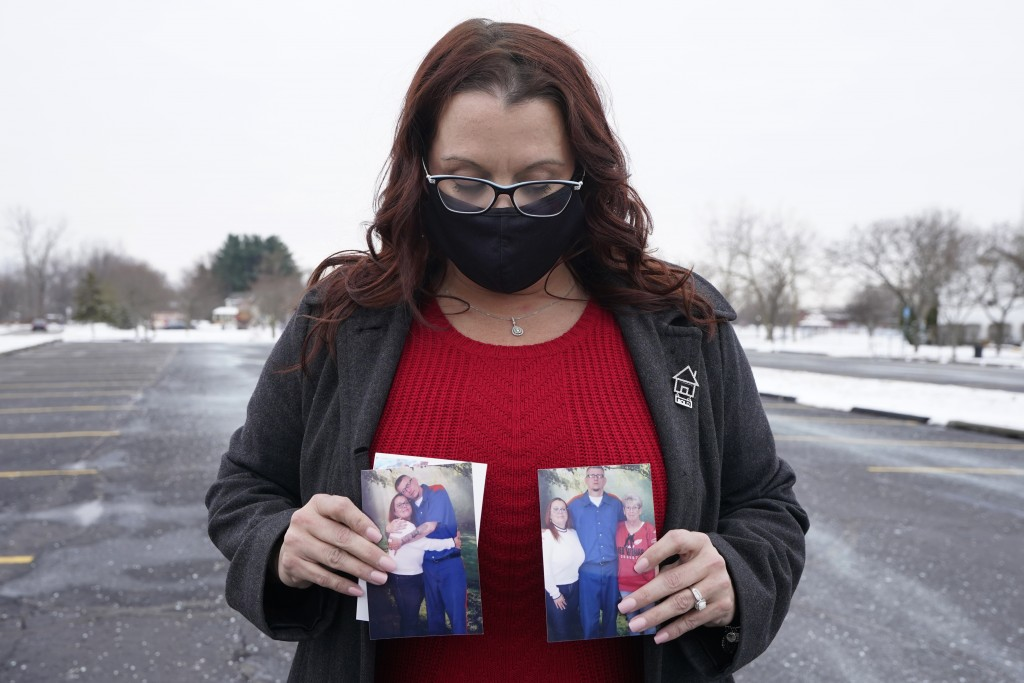 Jennifer Gross holds photos of herself with fiancé Robert Vermett, Friday, Dec. 18, 2020, in Taylor, Mich. Families of men incarcerated at Michigan's ...