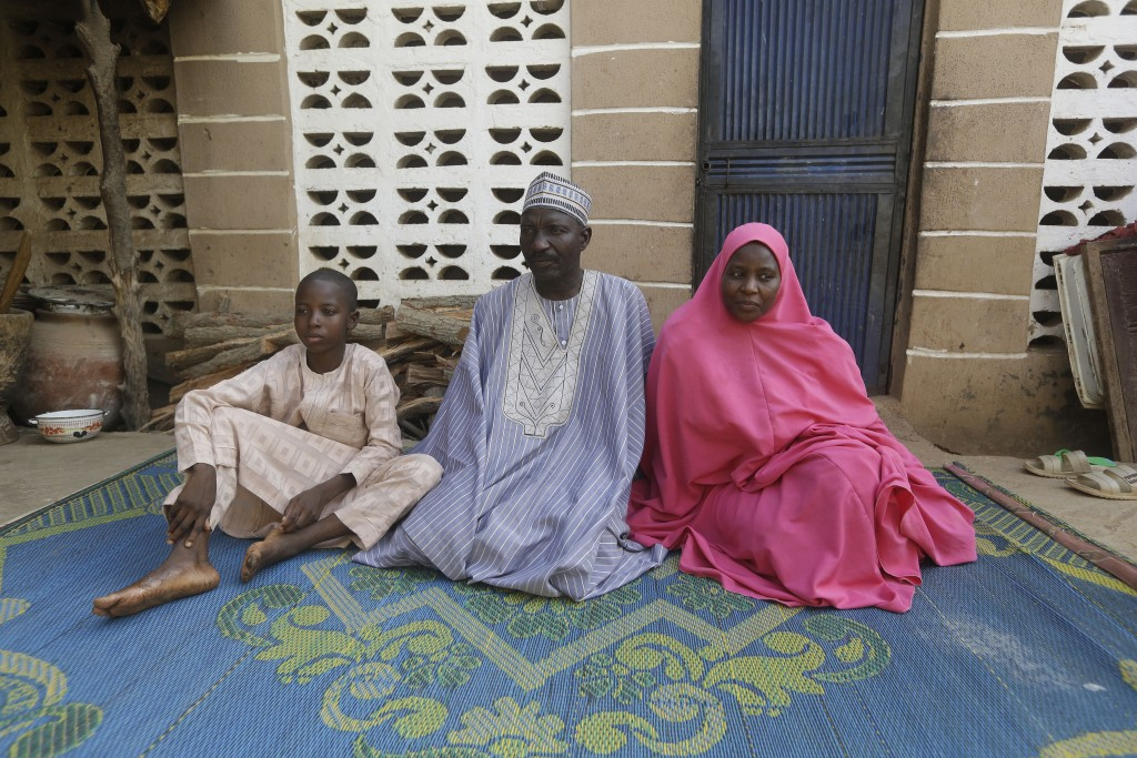 Usman Mohammad Rabiu, a 13 year old student of Government Science Secondary School Kankara, sits with his father Wada Haske and his mother Asmau Hassa...