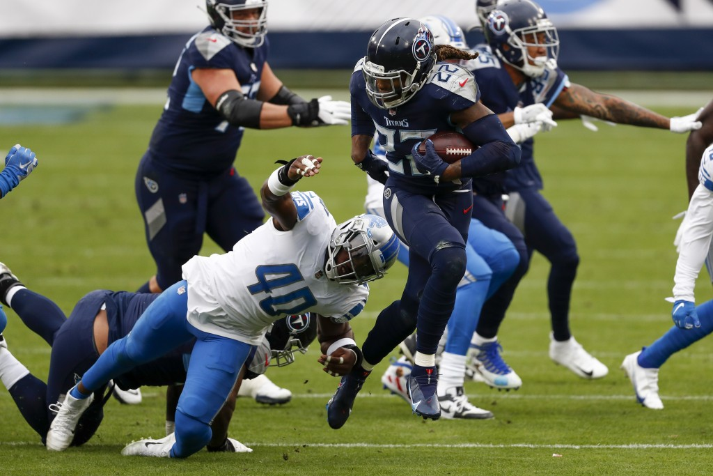 Tennessee Titans running back Derrick Henry (22) breaks away from Detroit Lions middle linebacker Jarrad Davis during the first half of an NFL footbal...