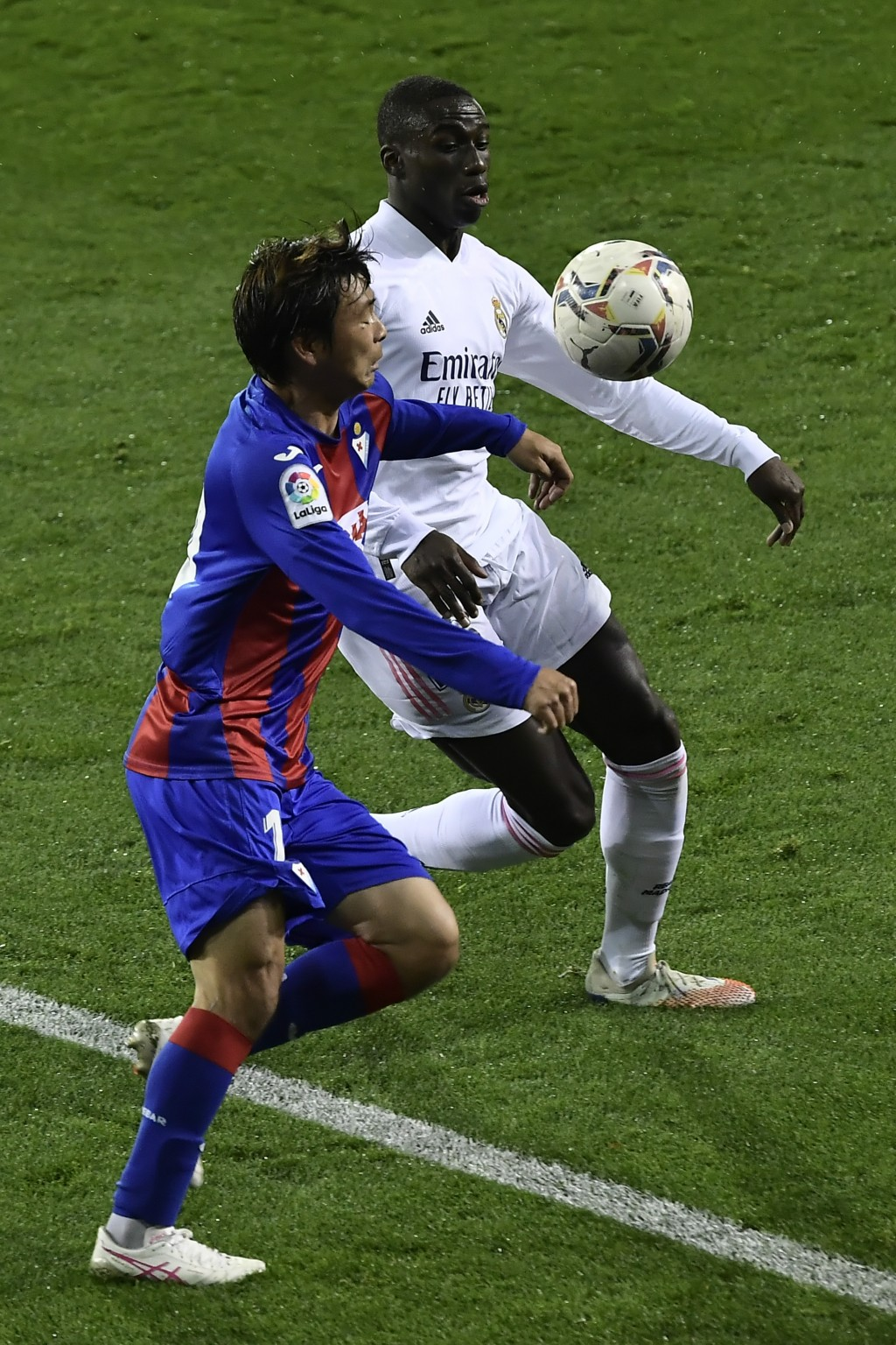 Real Madrid's Ferland Mendy, right views for the ball with Eibar's Tasahi Inui during the Spanish La Liga soccer match between Eibar and Real Madrid, ...