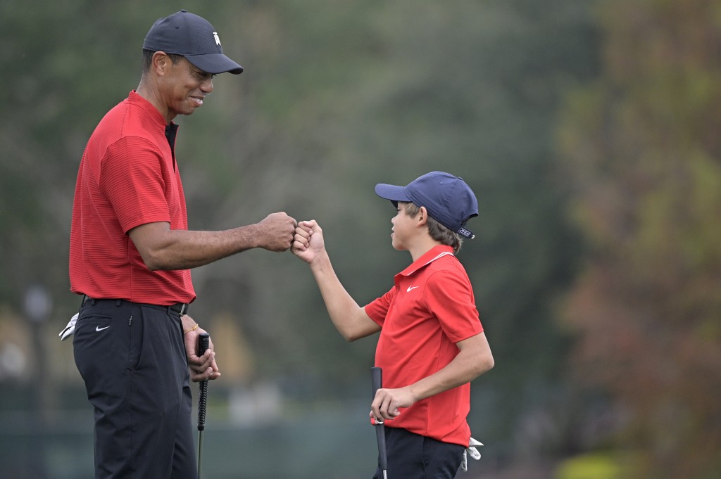 Tiger Woods, left, shares a fist-bump with his son Charlie after putting on the 18th green during the final round of the PNC Championship golf tournam...