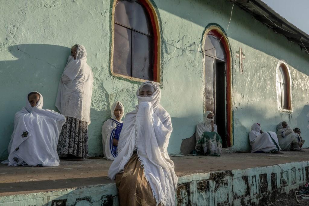 Women who fled the conflict in Ethiopia's Tigray region pray during Sunday Mass at a church, near Umm Rakouba refugee camp in Qadarif, eastern Sudan, ...
