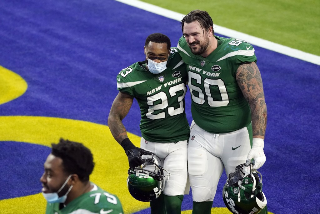 New York Jets cornerback Arthur Maulet (23) hugs center Connor McGovern (60) after a win over the Los Angeles Rams during an NFL football game Sunday,...