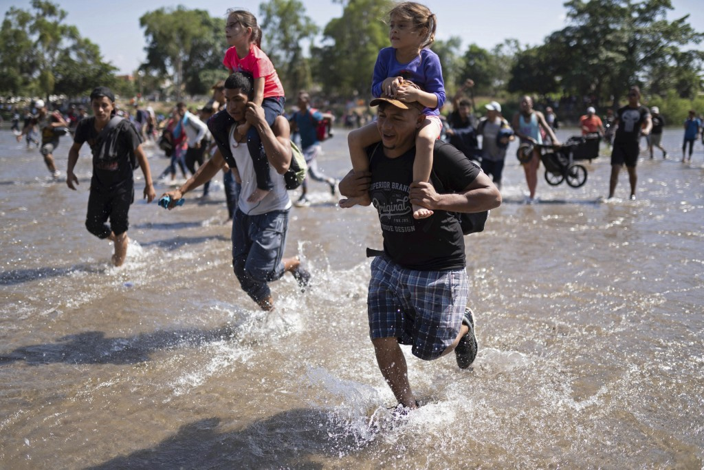 Central American migrants carry children across the Suchiate River from Guatemala to Mexico, near Ciudad Hidalgo, Mexico, Monday, Jan. 20, 2020, in ho...