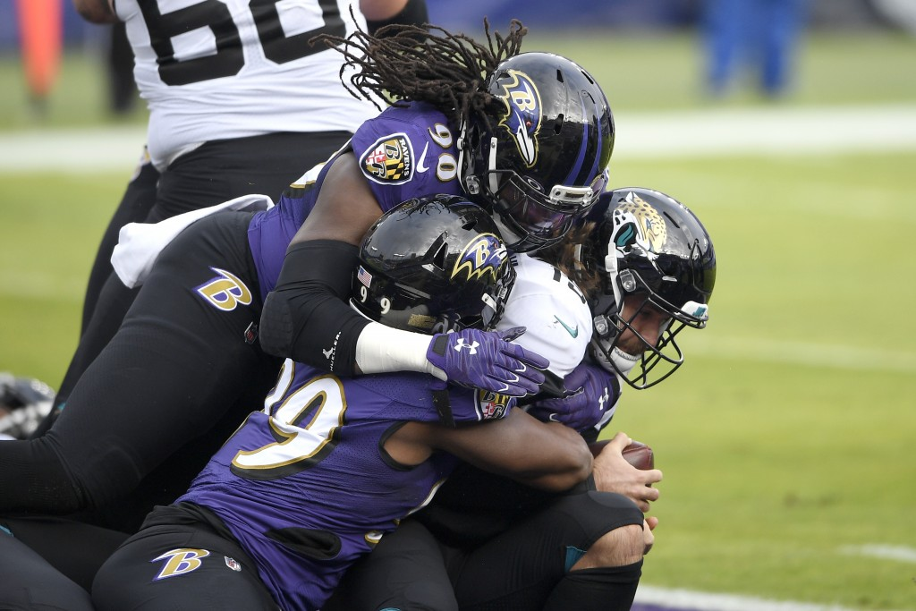 Jacksonville Jaguars quarterback Gardner Minshew II, right, is sacked for a safety by Baltimore Ravens linebacker Pernell McPhee (90) and linebacker M...
