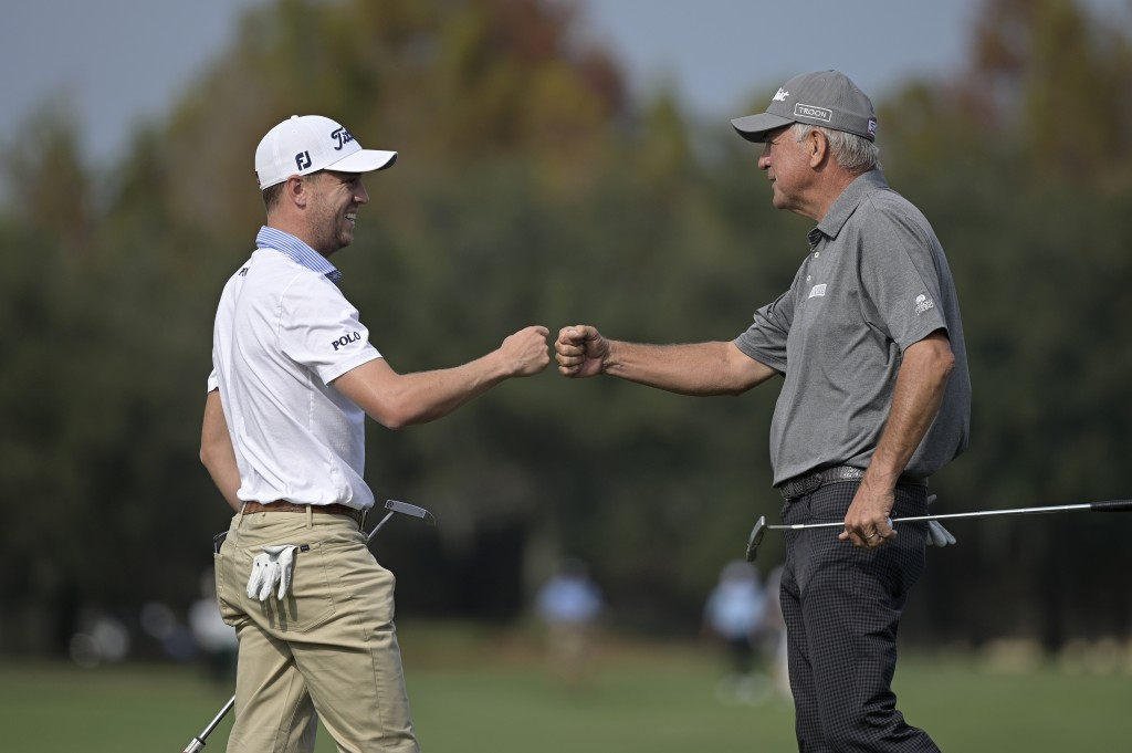 Justin Thomas, left, and his father Mike Thomas exchange fist-bumps after finishing on the 18th green during the final round of the PNC Championship g...