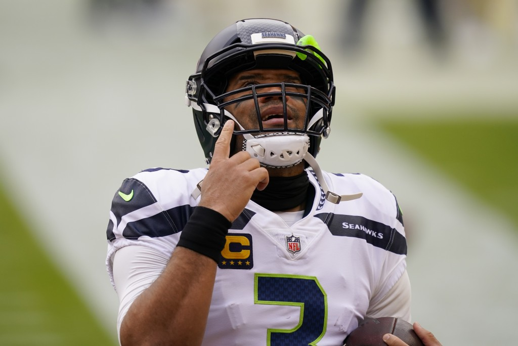 Seattle Seahawks quarterback Russell Wilson (3) points upwards before the start of the first half of an NFL football game against the Washington Footb...