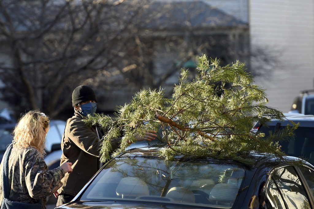 Parker Vivier and Marsden Olsen, both of Richmond, prepare to tie their tree to their car after purchasing from Frank Pichel's tree lot, Sunday, Dec. ...