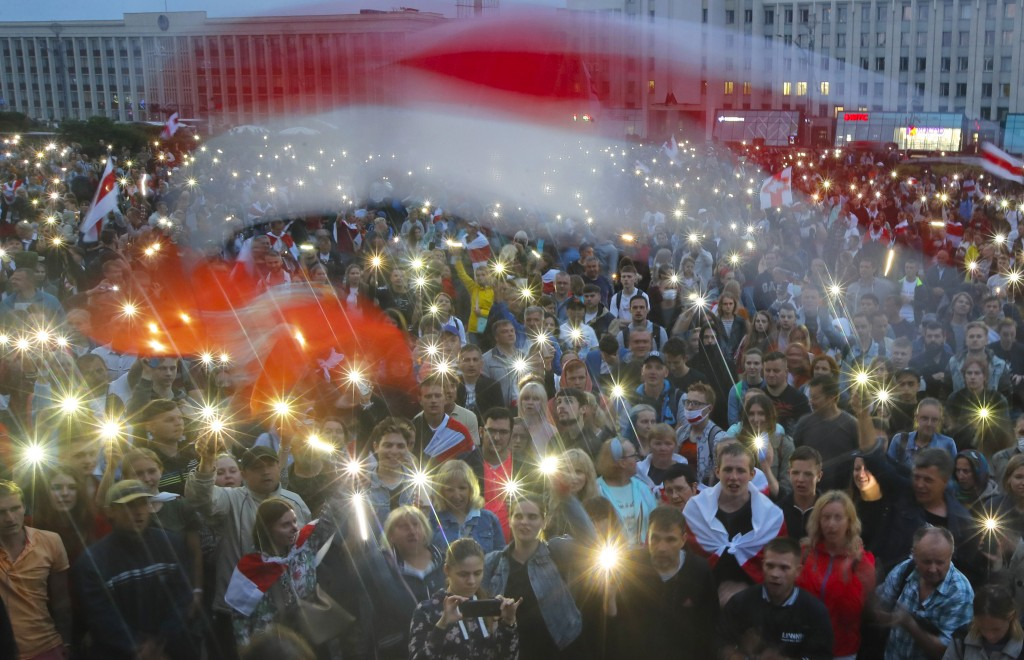 Belarusian opposition supporters activate the lights on their phones and wave old Belarusian national flags during a protest rally in front of the gov...