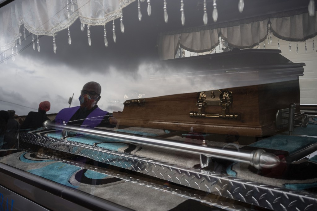 A funeral worker is reflected in the window of the car that carries 5-year-old Wandi Zitho's coffin in Orange Farm, South Africa, on April 28, 2020. T...