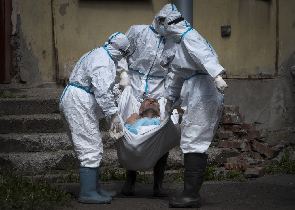 Medical workers wearing protective gear to protect against coronavirus infection, carry a patient at infectious diseases hospital where patients with ...