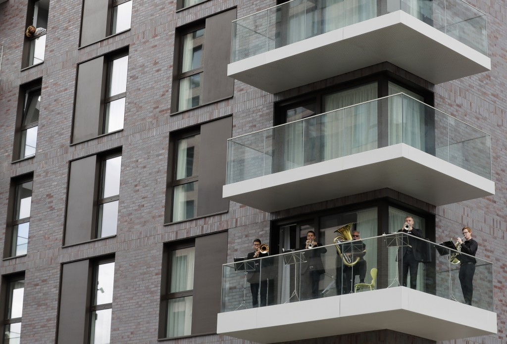 FILE - Musicians with the Royal Philharmonic Orchestra play from a balcony at Wembley Park in London, Saturday, Sept. 5, 2020. The Royal Philharmonic ...