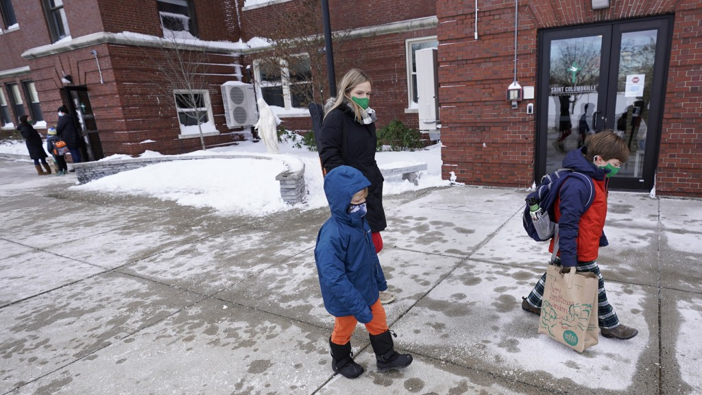 First grade student Landon Freytag, of Newton, Mass., right, walks with his mom, Kira, rear, and younger brother Declan as school is released for the ...