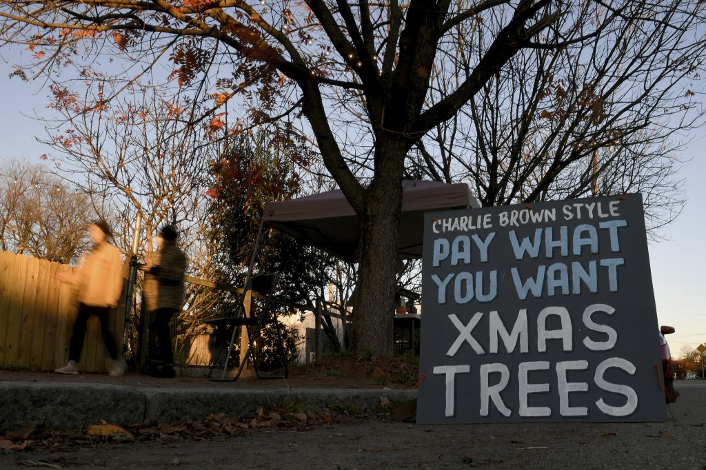 Pedestrians walk by Frank Pichel's tree lot, Sunday, Dec. 6, 2020, in Richmond, Va. A Virginia man has found a way to use Charlie Brown-style Christma...