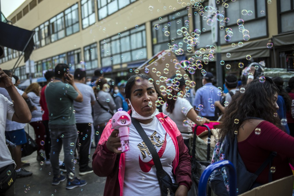 A street vendor sells a device that makes bubbles at the Mesa Redonda Market, a popular spot for Christmas shopping, amid the COVID-19 pandemic in Lim...