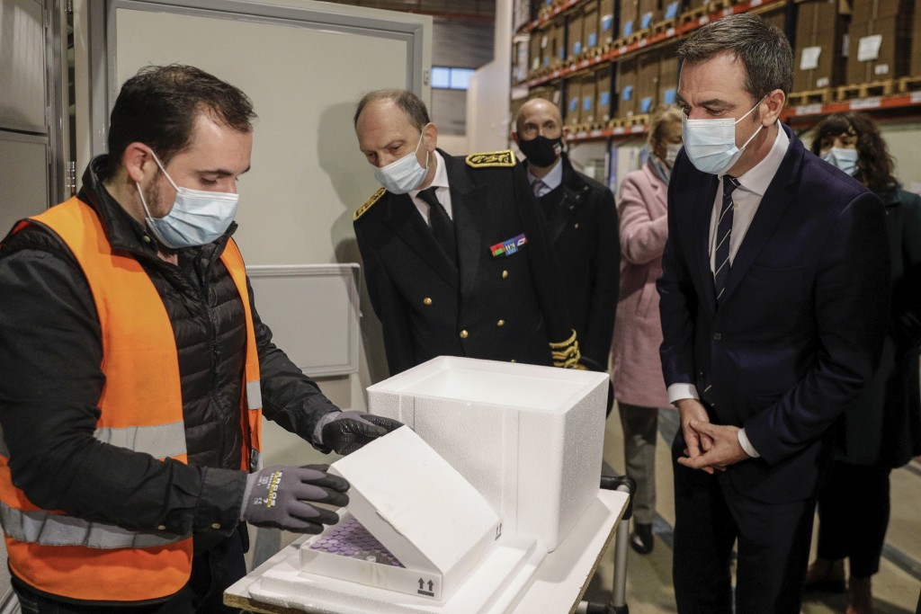 France's Health Minister Olivier Veran, right, looks on a boxe containing the Pfizer-BioNTech COVID-19 vaccine as he visits a distribution platform in...