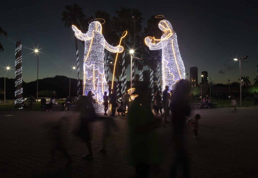 People look at illuminated Christmas decorations at a plaza in Caracas, Venezuela, Friday, Dec. 18, 2020. (AP Photo/Ariana Cubillos)