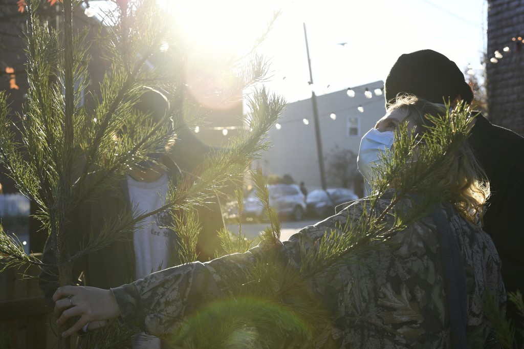 Parker Vivier (R), of Richmond, looks at a tree to buy at Frank Pichel's tree lot, Sunday, Dec. 6, 2020, in Richmond, Va. A Virginia man has found a w...