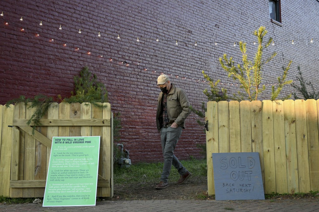 Frank Pichel prepares to close his tree lot after selling out of trees, Sunday, Dec. 6, 2020, in Richmond, Va. The Virginia man has found a way to use...