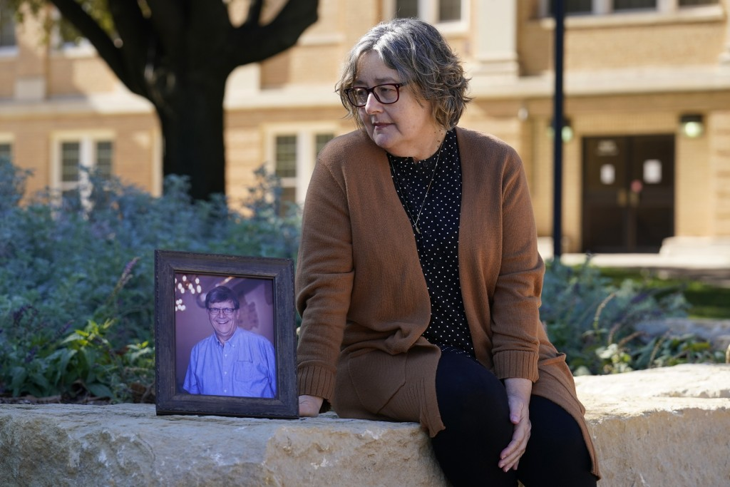 Debbie Riggs poses for a photo, sitting by a portrait of her late husband, Mark Riggs on the campus of Abilene Christian University, Wednesday, Dec. 1...