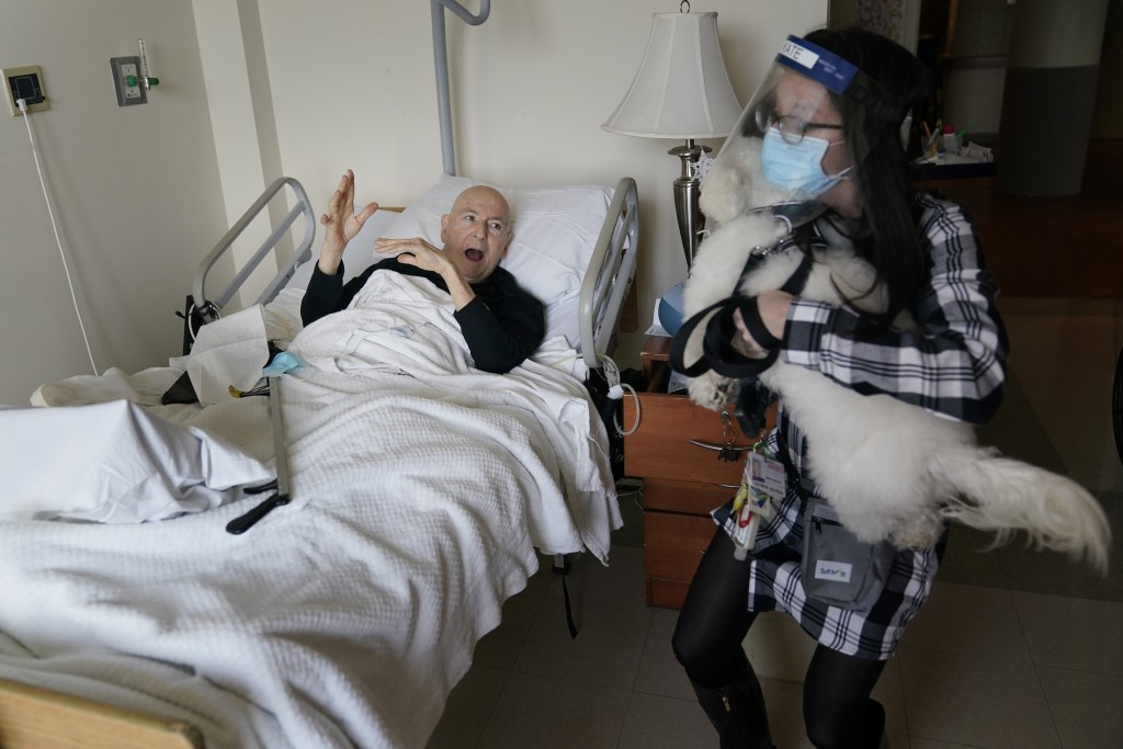 Jeff Philipson, 80, left, exclaims as therapeutic activities staff member Kate DelPizzo arrives for a visit with Zeus, a bichon frise, at The Hebrew H...