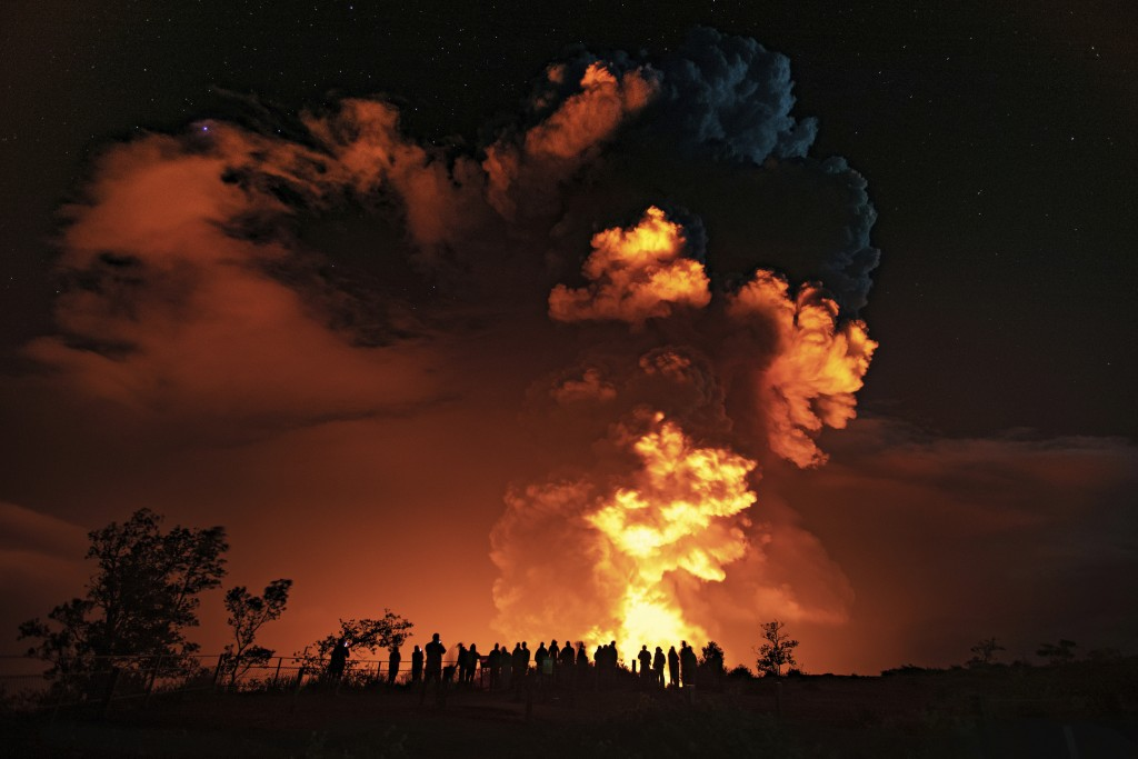 In this photo provided by the National Park Service, people watch an eruption from Hawaii's Kilauea volcano on the Big Island on Sunday, Dec. 20, 2020...