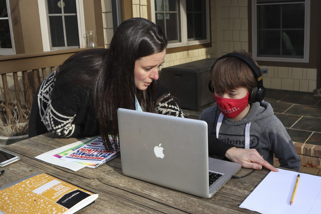Angela Atkins helps her son Jess Atkins work on a math problem on his laptop during home schooling at their home in Oxford, Miss., on Dec. 18, 2020. A...