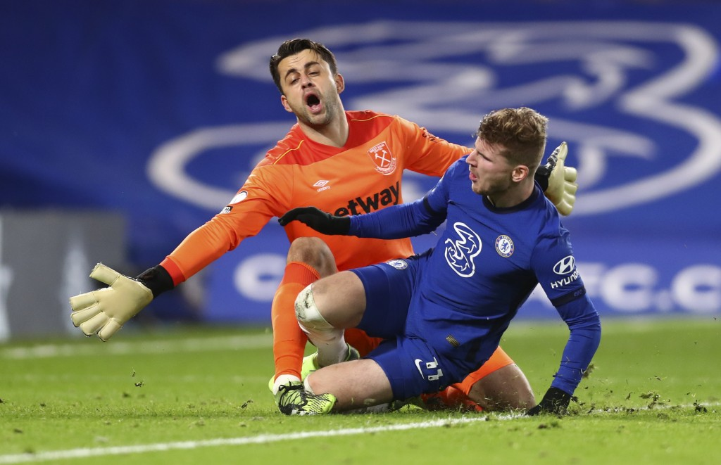 Chelsea's Timo Werner, right, collides with West Ham's goalkeeper Lukasz Fabianski during the English Premier League soccer match between Chelsea and ...