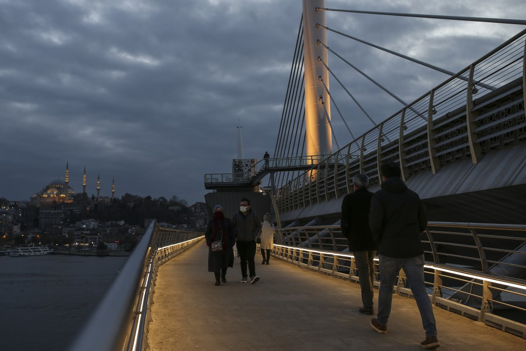 People walk on the Halic Bridge over the golden Horn in Istanbul, Monday, Dec. 21, 2020. Turkey has become one of the worst-hit countries in the world...