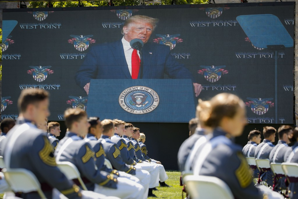 FILE - In this June 13, 2020, photo, President Donald Trump is shown on a video screen as he speaks to United States Military Academy graduating cadet...