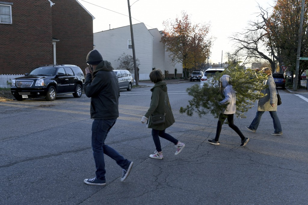 From left, Peter Taffs, Marcie Taffs, 14, Juno Taffs, 11, and Clare Van Loenen walk across the street after buying a tree from Frank Pichel's tree lot...