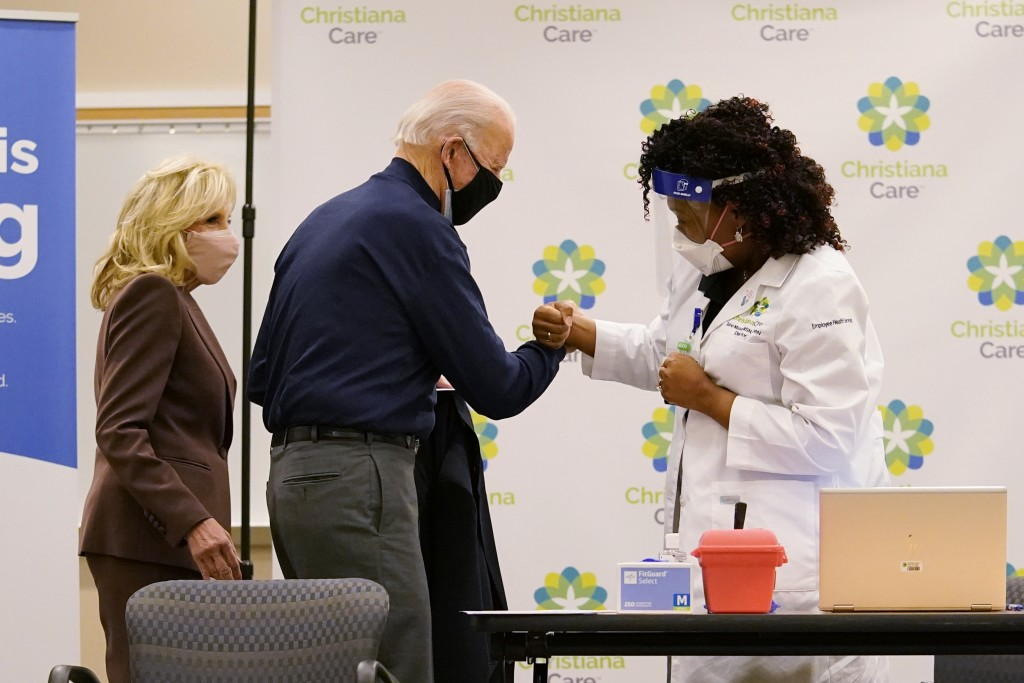 President-elect Joe Biden fist bumps with nurse practitioner Tabe Mase after receiving his first dose of the coronavirus vaccine at ChristianaCare Chr...