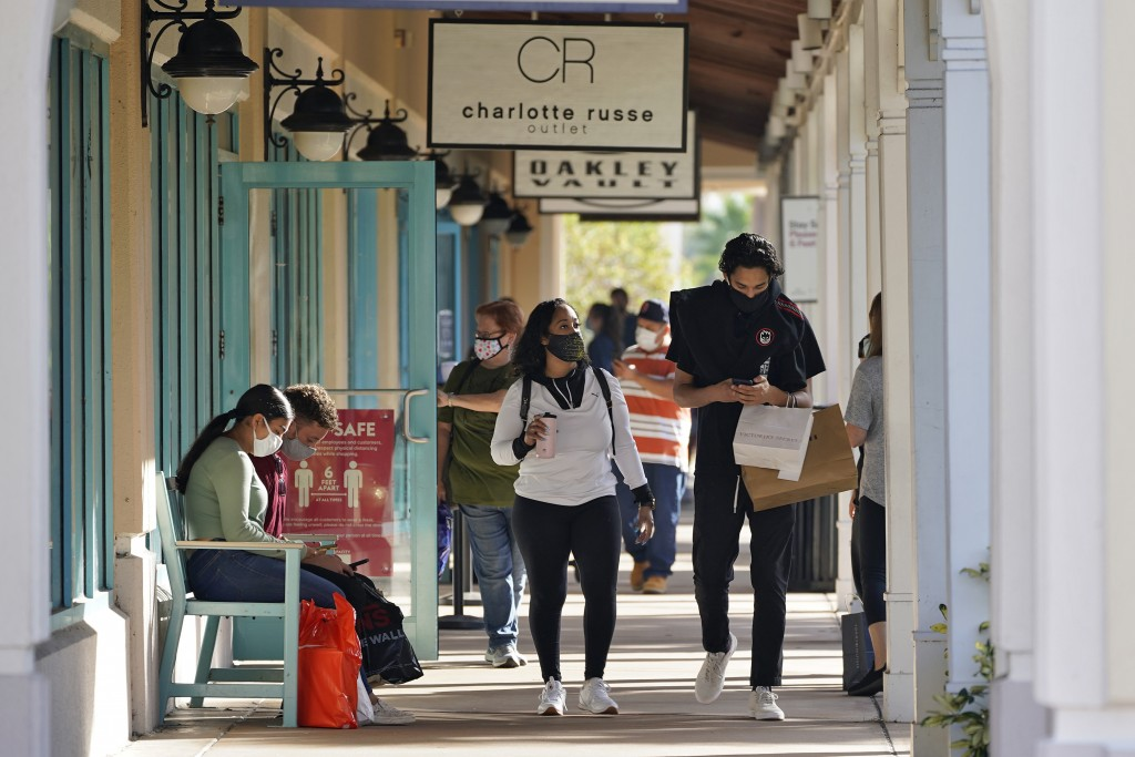 FILE - Shoppers wear protective face masks as they look for Black Friday deals at the Ellenton Premium Outlet stores Friday, Nov. 27, 2020, in Ellento...