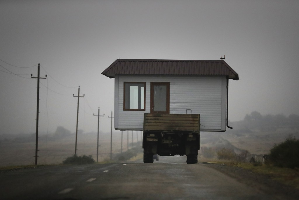 A family drives a truck loaded with a small house along a highway as they leave their home village in the separatist region of Nagorno-Karabakh, Wedne...