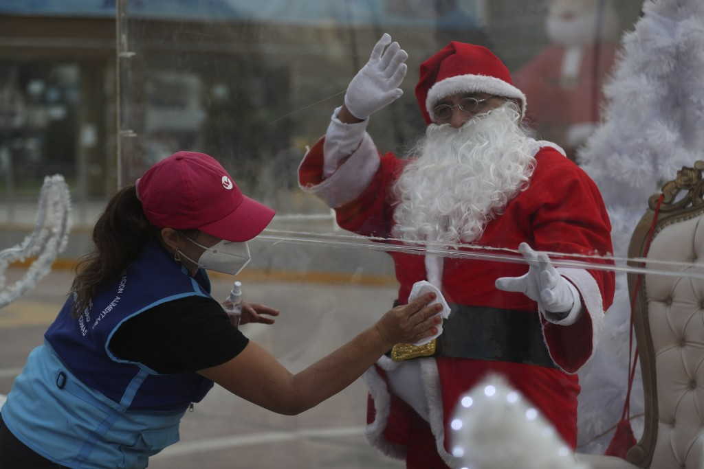 Dressed as Santa Claus, David Pizarro waves from inside a plastic enclosure as a woman disinfects it in an effort to curb the spread of COVID-19, at a...