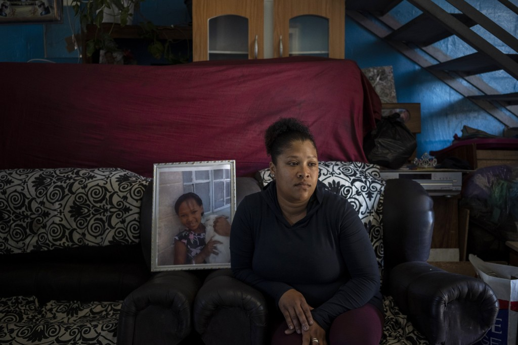 Carmen van Wyk sits on a sofa in her house next to a framed photograph of her daughter, Tazne, in Cape Town, South Africa, on Sept. 10, 2020. The 8-ye...