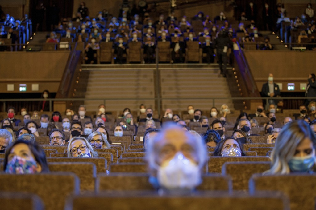 FILE - Guests wear face masks and sit at a safe distance as they follow the opening ceremony of the 77th edition of the Venice Film Festival at Venice...