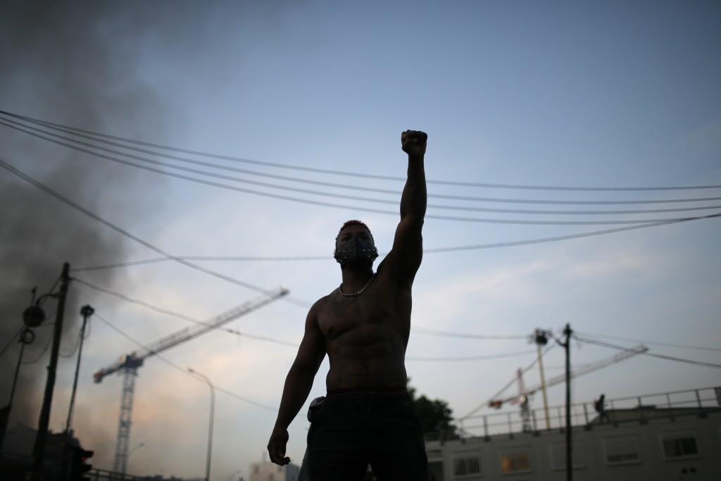 A protester raises his fist during a demonstration Tuesday, June 2, 2020. Paris riot officers fired tear gas as scattered protesters threw projectiles...