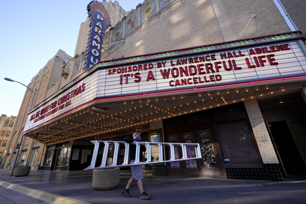 Employee Grayson Allred walks away with a ladder after working on the front marquee at the Paramount Theatre on Wednesday, Dec. 16, 2020, in Abilene, ...