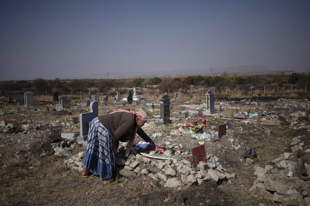 Rebecca Mohapi, who's son Onthatile died last year, puts one of his favorite toys on his grave in Damonsville, South Africa, on June 8, 2020. She beli...