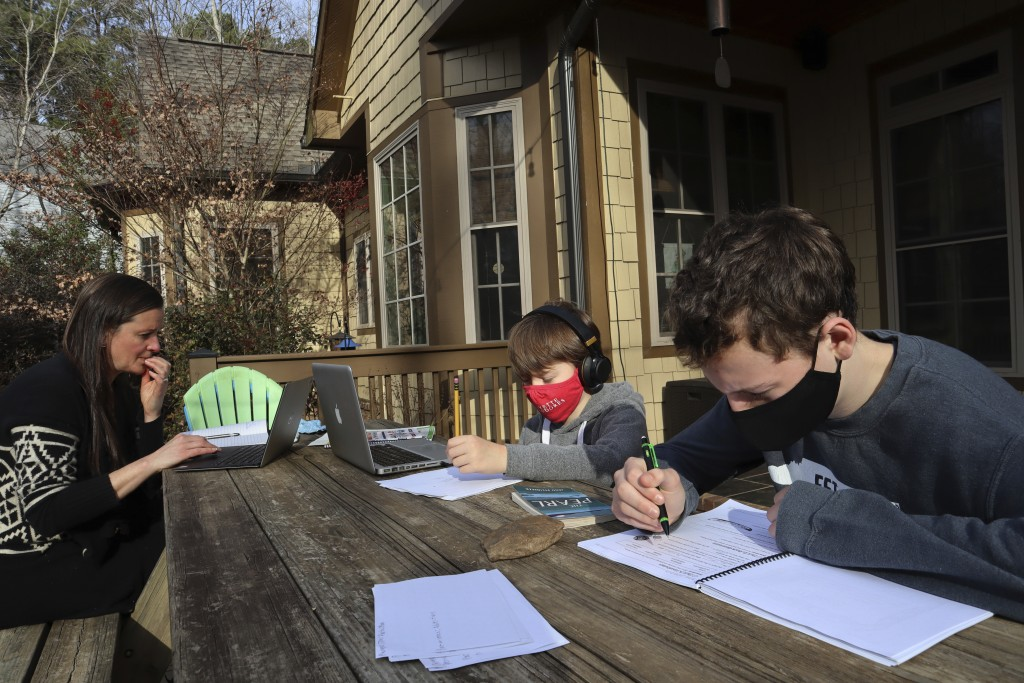 Angela Atkins works outside her home in Oxford, Miss., on Dec. 18, 2020 while her two sons, Jess and Billy, focus on schoolwork. Atkins is home school...