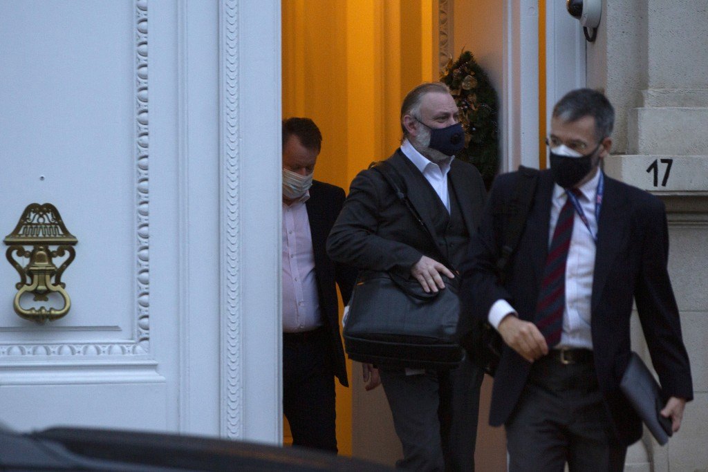 Britain's chief negotiator David Frost, left, and British Ambassador to the EU Tim Barrow, center, leave the UK ambassadors residence in Brussels, Tue...