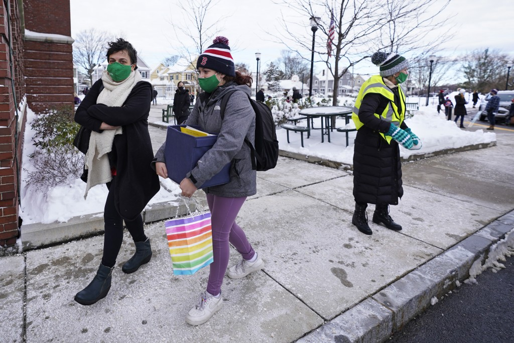 Eighth grade student Madeline Perry, of Brookline, Mass., center, walks with her mom, Danna, left, while leaving to go home after an in-class school d...